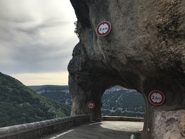 Wide shot of a route under an arch rock surrounded by mountains covered with trees