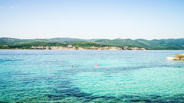Wide shot of a sea with buildings on the shore and forested mountains in the distance
