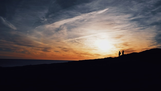 Wide shot of silhouettes of two people walking on a hill with the sun shining
