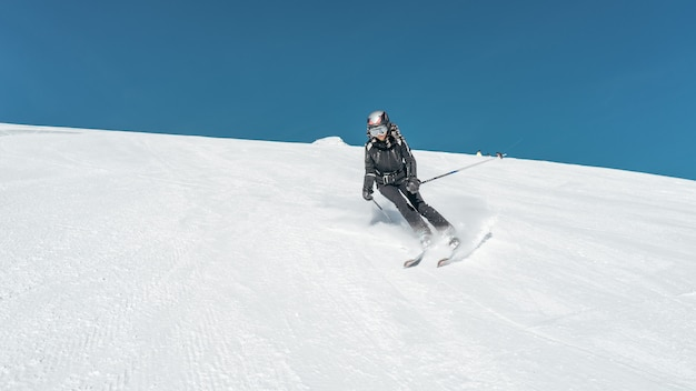 Wide shot of a skier skiing on a snowy surface wearing skiing outfit and helmet