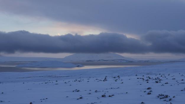 Wide shot of a snowy shore near frozen water under a cloudy sky