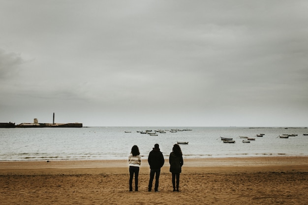 Wide shot of three people standing near the seashore with small boats floating in the sea