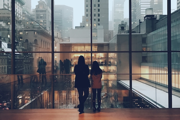 Wide shot of two females standing at a huge glass window looking at the view of high rise buildings