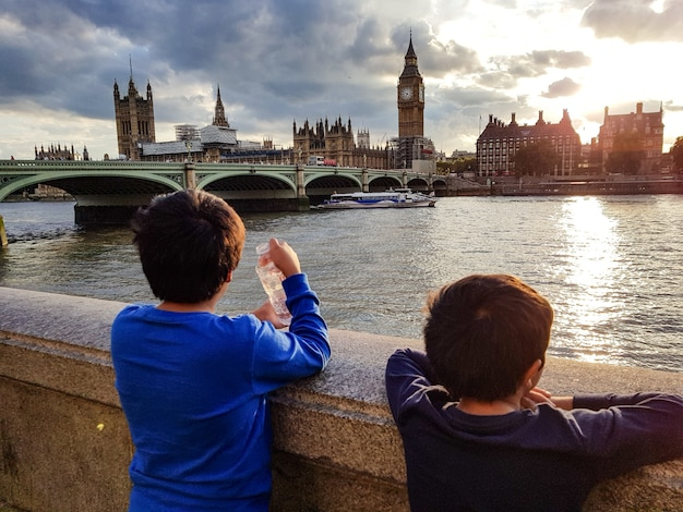 Wide shot of two young boys enjoying the view of beautiful architecture from a bridge