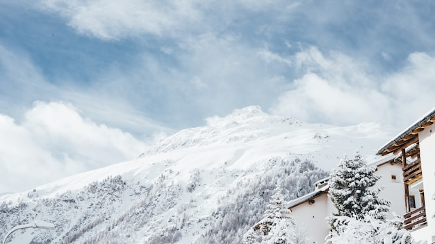 Wide shot of a white and brown house near trees and a mountain covered in snow