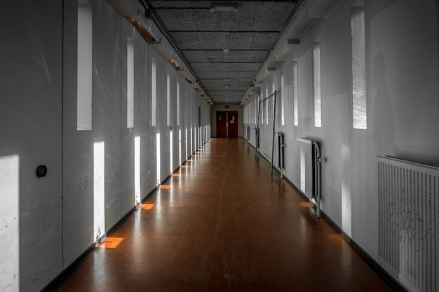 Wide shot of a white hallway with reflections of light from windows