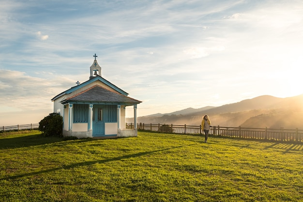 Wide shot of a woman walking next to a little chapel on a cliff during the sunrise Premium Photo