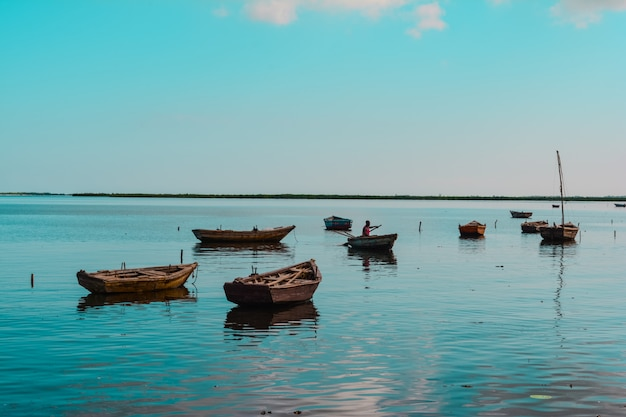 Wide shot of wooden small boats in the water with an african-american person in one of them