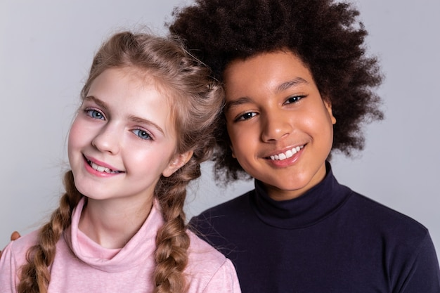 Wide smile. appealing pretty children standing together and hugging while having grey background