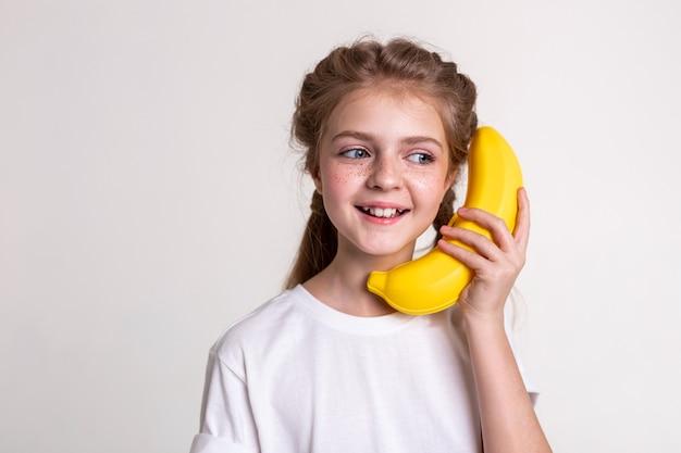 広い笑顔。プラスチック製のバナナを運び、深刻な電話のふりをしている青い目をしたうれしそうな長髪の子供