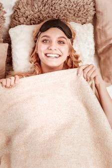 広い笑顔。睡眠の準備をし、毛布をいたるところに持っている貴重な長髪の女性