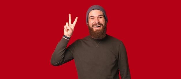 활짝 웃고 있는 수염난 남자가 카메라를 향해 평화나 승리의 몸짓을 하고 있다.
