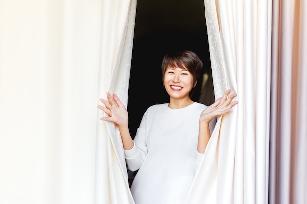 Wide smiling beautiful asian woman opens curtains on window.