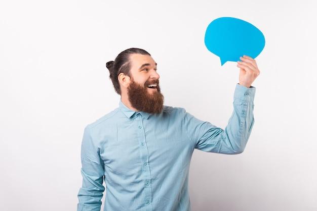Широко улыбающийся человек смотрит на голубую речь пузыря, которую он держит.
