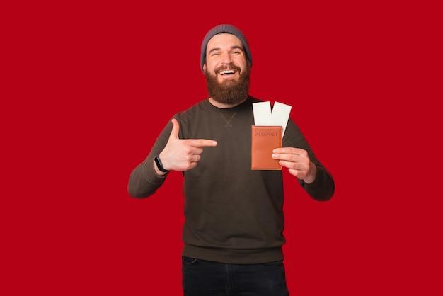 활짝 웃는 남자가 들고 있는 티켓으로 여권을 가리키고 있다.