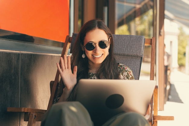 Wide smiling woman is saying hi to the person he is talking on her laptop.