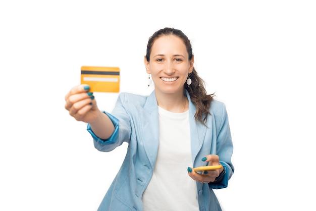 활짝 웃는 여성이 신용카드와 휴대전화를 카메라에 보여주고 있습니다.
