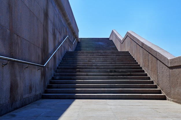 Wide stone staircase. way up to blue sky in sunny day. concept of hope and bright future. freedom, career or success concept. granite stairs.