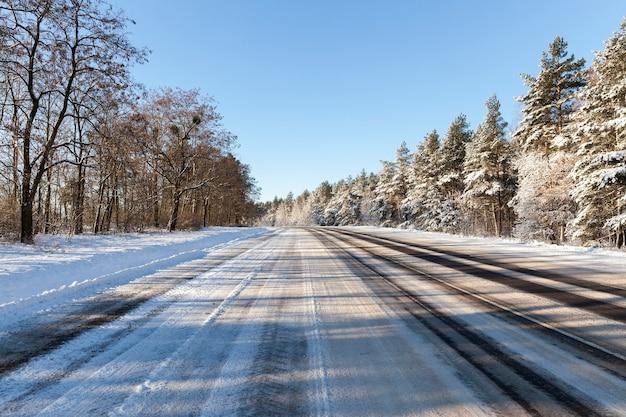 冬季の広くまっすぐなアスファルト道路と車道の車からの轍、雪の下の木々、日中の風景と晴天