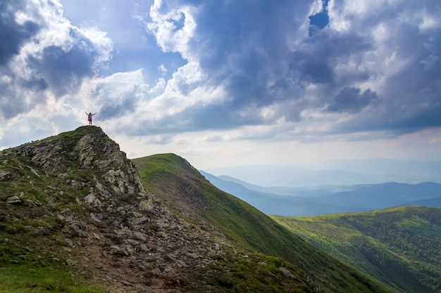 Wide summer mountain panorama. small silhouette of tourist with backpack and raised arms on rocky mountain top against bright blue white cloudy sky. beauty of nature, tourism and traveling concept.