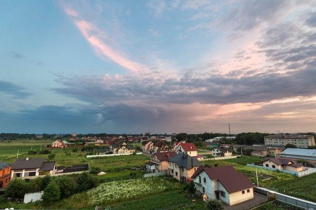 Wide summer panorama of new quiet residential suburban area. land plots and new modern houses among green trees under cloudy sky at sunset. construction, selling and investment in real estate concept.