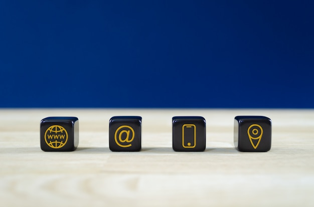 Wide view of customer service image with four black dices with gold contact information and location icons on them. over blue background.