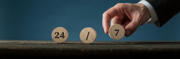 Wide view image of a hand of a businessman assembling a 24/7 sign with wooden cut circles.