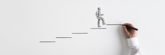 Wide view image of male hand drawing businessman walking up the stairs towards success.