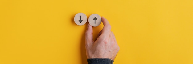 Wide view image of male hand placing two wooden cut circles with arrows pointing up and down on yellow.