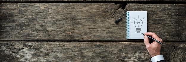 Широкоформатное изображение бизнесмена, рисующего лампочку в блокноте на деревенской деревянной доске