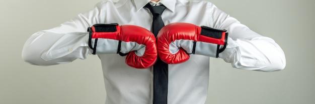 ビジネスの力と決意の概念的なイメージで彼の拳を一緒にぶつけてボクシンググローブを着用しているビジネスマンのワイドビュー画像。