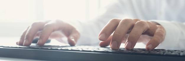 사무실 창에서 나오는 태양 플레어와 함께 검은 키보드를 사용하여 입력하는 컴퓨터 프로그래머의 와이드 뷰 이미지.
