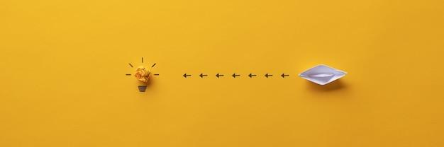 概念的なイメージで電球に向かって航行する紙製の折り紙ボートのワイドビュー画像。