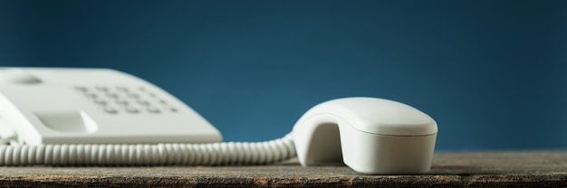 Wide view image of white landline telephone handset of the hook