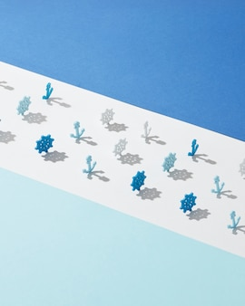 Wide white lane with plastic toys of marine wheels and anchors shadows on a light blue wall, copy space.