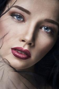 Вдова в вуали, портрет молодой женщины брюнет на темном фоне. загадочный яркий образ женщины с профессиональным макияжем. покрывало на женском лице