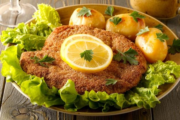 Венский шницель с картофелем и салатом, выборочный фокус.