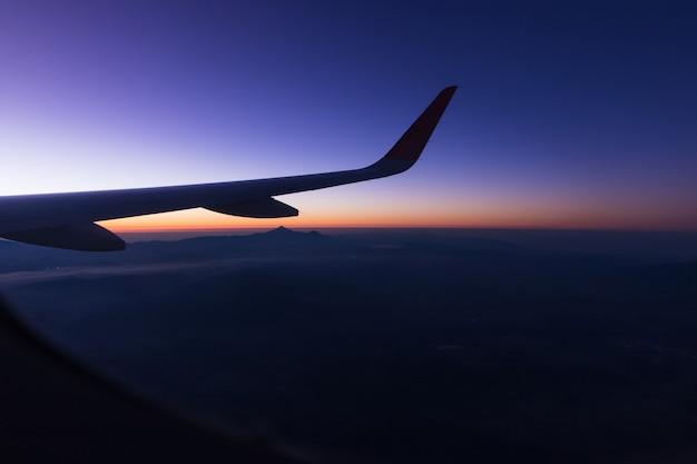 カンクンの地域で背景に山とウィンドウ飛行機wiewの日の出