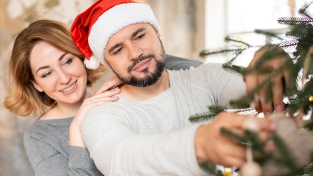 Жена и муж вместе украшают елку