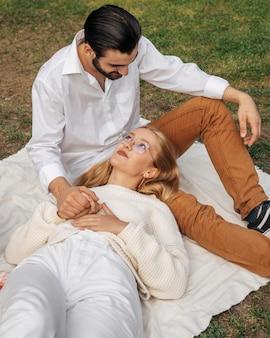 ピクニックで一緒にかわいい瞬間を楽しんでいる妻と夫