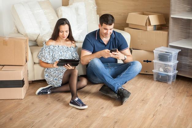 タブレットで家具の世話をしている妻と夫。美しい若いカップル