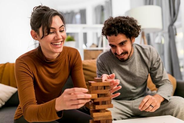 Жена и муж играют в деревянную башню