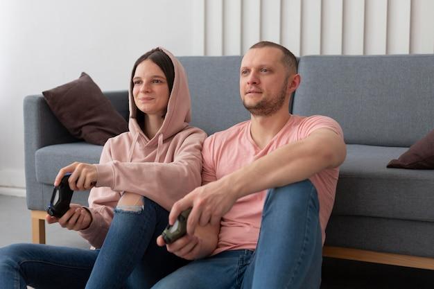 Жена и муж вместе играют в видеоигры дома