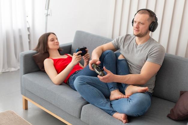 家で一緒にビデオゲームをしている妻と夫