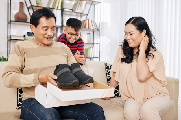 Жена и сын смотрят на счастливого возбужденного мужчину средних лет, открывающего картонную коробку с кроссовками, которые он так хотел
