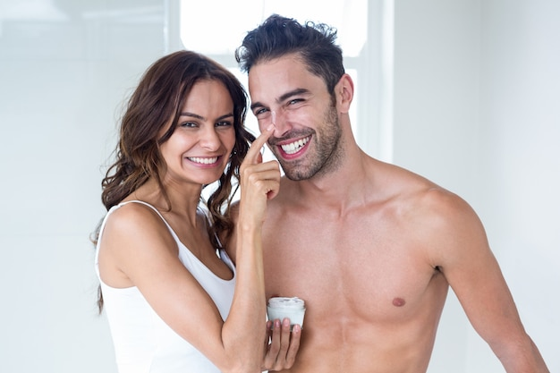Wife applying cream on husband face at home