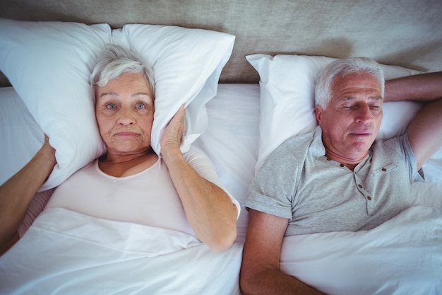Wife blocking ears with pillow while husband snoring on bed
