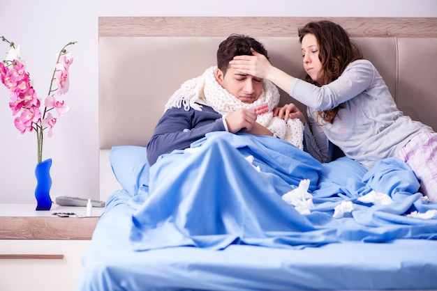 Wife caring for sick husband at home in bed