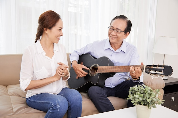 Wife clapping to husband playing guitar