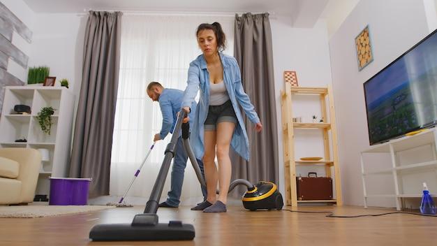 아파트 바닥에서 진공 청소기로 먼지를 청소하는 아내.